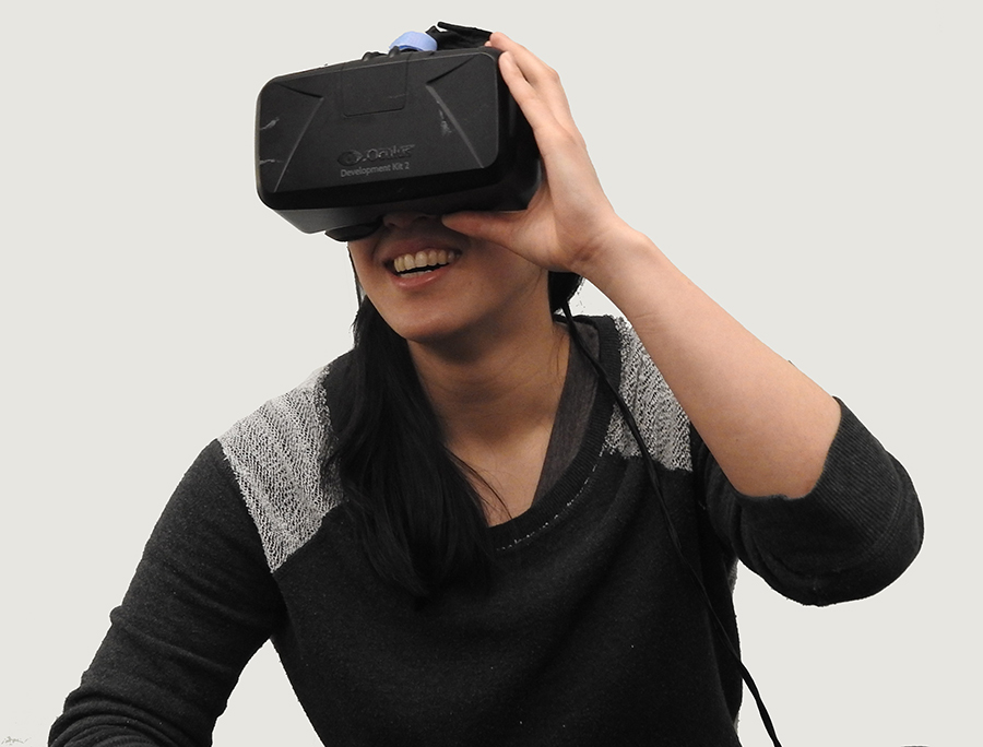 Person with long hair and black shirt looking through a VR device