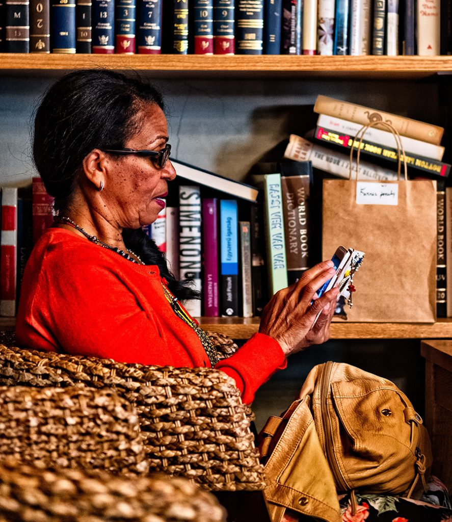 Woman wearing a red jumper on her phone surrounded by books